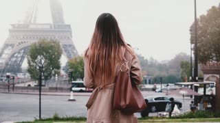 Young stylish woman taking photo of Eiffel tower in fog on smartphone. Girl traveling in Paris, France alone.