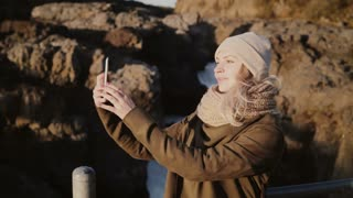 Young stylish woman taking selfie photos on smartphone. Traveling female captures happy memories and view.