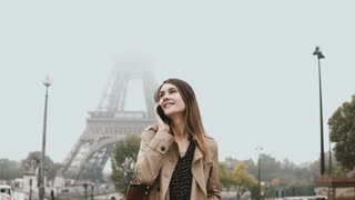 Young stylish woman walking near the Eiffel tower in Paris, France and talking on mobile phone with friends.