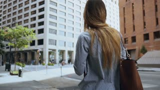 Young successful businesswoman walking through the financial district at work in office in sunny day. Slow motion.