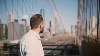 Young successful Caucasian businessman stands looking around, smiling happy and crosses arms at Brooklyn Bridge 4K.