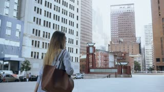Young successful female holding the documents and walking to work in office in New York, America. Slow motion.