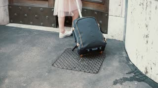 Young traveler woman walking with a suitcase in the street. Girl opens the door and comes into an arch.