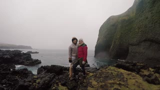 Young traveling couple in raincoats standing on the shore of the sea and enjoying the trip. Tourists man and woman.