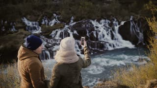 Young traveling couple standing in mountains valley near waterfall and talking pictures or selfie photos on smartphone.