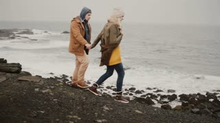Young traveling couple walking on the shore of the sea. Attractive man and woman kissing near the water.