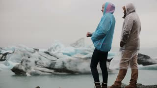 Young traveling couple wearing raincoats enjoying the view in ice lagoon in Iceland. Tourists on the nature at cold day.