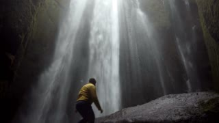 Young traveling man walking near the powerful Gljufrabui waterfall in Iceland. Male jumping of joy and happy.