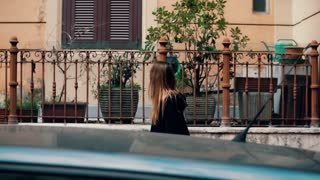 Young traveling woman exploring the new city. Attractive girl walking on the old town and looking around. Slow motion.