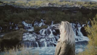 Young traveling woman standing near the waterfalls in Iceland and smiling. Girl raising hands up and feeling happy.