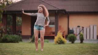 Young woman dancing on the backyard on sunny summer day. Teenager have fun outside, spending leisure for hobby.