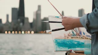 Young woman drawing the picture on the shore of Michigan lake, Chicago, America. Street artist using brushes and paint.