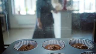Young woman opens the oven and gets out the baking tray for cupcakes. Attractive female cooking desserts. View inside.