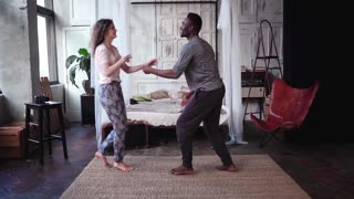 Young woman running through the room and jumping on man hands. Multiethnic couple in pajamas hugs and kisses.