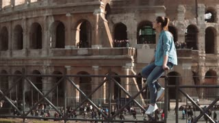 Young woman sits on fence against background of Colosseum in Rome, Italy in sunny day. Female swings legs. Slow motion.