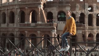 Young woman sits on fence looking at Roman Colosseum in Italy. Girl enjoys the vacation in Rome. Slow motion.
