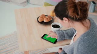 Young woman sitting at the table and drinking coffee in kitchen. Brunette girl uses smartphone, green screen.