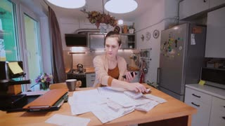 Young woman sitting at the table in kitchen and calculating bills. Home accounts department. Checking the bills.