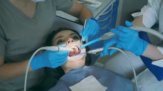 Young woman sitting in the dental chair with opening wide mouth. Dentist with nurse clean and polish teeth.