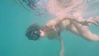 Young woman snorkeling in the tropical sea. Girl in bikini swimming with mask underwater. slow motion.