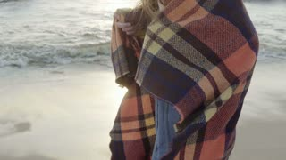 Young woman standing on shore of sea and looking into the distance. Lonely female enjoy the beach, waves in cold day.