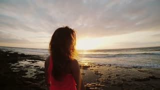 Young woman standing on the stony coast and enjoying the sunset. Wing blowing her hair. Girl on evening beach.