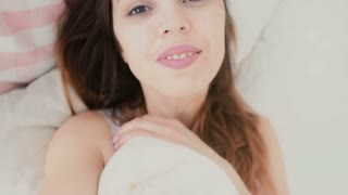 Young woman taking selfie, using phone in the bedroom. Smiling and tender female in the morning. Slow motion.