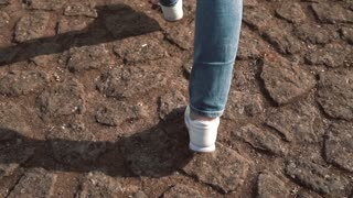 Young woman tourist runs on steps in Rome, Italy in sunny day, taking pictures of Colosseum on smartphone. Slow motion.