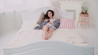 Young woman using wireless technology lying on the bed and typing on touchscreen. Girl browses the Internet in morning.
