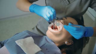 Young woman visiting the dental office. Female lying in dental chair, doctor polishing and cleaning her teeth.