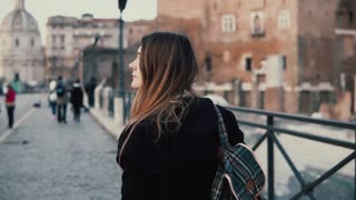 Young woman walking in city centre, Roman Forum. Female traveler takes photo of old town ruins. Girl exploring Italy.