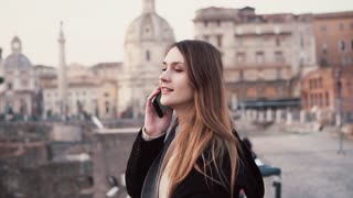 Young woman walking in city centre, Roman Forum. Female traveler talking on the phone. Girl exploring Italy.