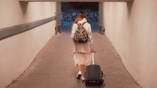 Young woman walking through tunnel carrying the suitcase. Girl with backpack walking the city, traveling. Slow motion.