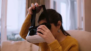 Young woman wearing VR-headset glasses of virtual reality at home, sitting on sofa.