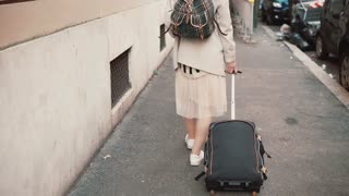 Young woman with suitcase and backpack going through the building in the city. Girl with baggage moving to new place.