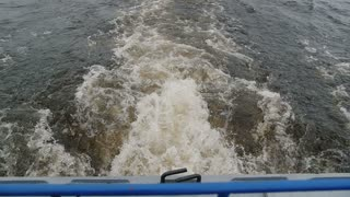 Water splashes from underneath a motor. Sprays of water in a lake, river, sea, ocean.