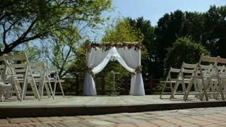 Wedding arch and white chairs in the open air