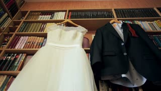 Wedding dress and suit hanging on a hangers