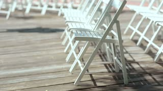 White chairs on a wooden platform in the open air