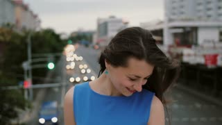 Wind blows long dark hair beautiful young women. happy, smiling girl standing on the bridge and looks at the camera. 4K