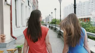 Wind blows long dark hair beautiful young women walking down the street past the shops, back view, slow mo stedicam shot