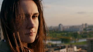 Wind blows long dark hair. girl standing on the roof smiling, looking at the camera. close up. Slow motion