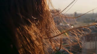 Wind blows long dark hair. girl standing on the roof with his head down. close up. Slow motion