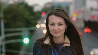 Wind blows long hair beautiful young women. smiling girl standing on the bridge in the evening and looks at camera. 4K