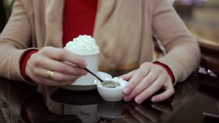 woman adds marshmallows in your coffee with cream
