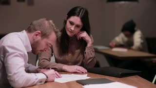 woman and man working with documents in cafe