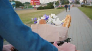 Woman hands on handlebar of bike with flowers and bread in basket as she walks in the street, slow mo, steadicam shot