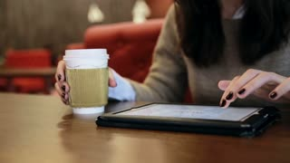 woman hands using tablet touchscreen in cafe