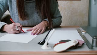 Woman holding pencil, sitting at the table and drawing sketch on paper. Erase in outline. Slider left, front view. 4K