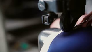 Woman making a smooth seam on sewing machine. Worker sew leather for shoe production. Lady sewing pieces together. 4K